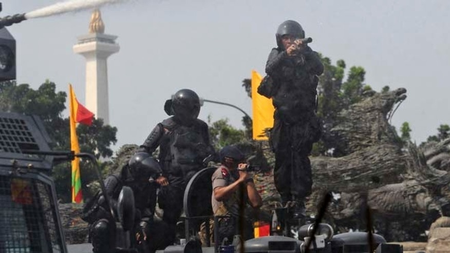 Aug. 21, 2014: A riot police officer prepares to fire his tear gas launcher during a clash with supporters of losing presidential candidate Prabowo Subianto near the Constitutional Court in Jakarta, Indonesia. (AP)