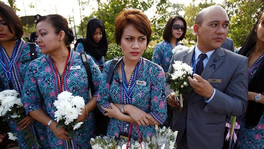 Malaysia Airlines crew members hold flowers as they wait outside Bunga Raya Complex at Kuala Lumpur International Airport where victims' bodies of the ill-fated Malaysia Airlines Flight MH17 is scheduled to be flown back, in Sepang, Malaysia, Friday, Aug. 22, 2014. The remains of at least 15 Malaysians killed when the jetliner was shot down over Ukraine will be returned to their home country this week, the first Malaysian victims of the disaster to be flown home, the country's defense minister said Tuesday.(AP Photo/Lai Seng Sin)