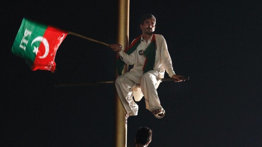 "A supporter of Pakistan's cricketer-turned-politician Imran Khan climbs on a pole and listens to his leader's speech during a protest in Islamabad's high-security ""Red Zone,"" in Islamabad, Pakistan, Wednesday, Aug. 20, 2014. Pakistan's powerful army chief Gen. Rasheel Sharif asked the government to hold negotiations with protesters to settle a mass demonstration outside parliament, officials said. (AP Photo/Anjum Naveed)"