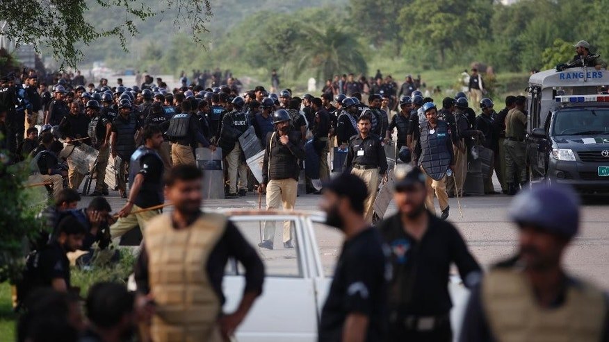 "Police forces deploy outside the secretariat block in Islamabad, Pakistan, Wednesday, Aug. 20, 2014. Tens of thousands of protesters entered Islamabad's high-security ""Red Zone"" the night before, five days after arriving in the capital. Pakistan's powerful army chief Gen. Rasheel Sharif asked the government to hold negotiations with protesters to settle a mass demonstration outside parliament, officials said. (AP Photo/B.K. Bangash)"