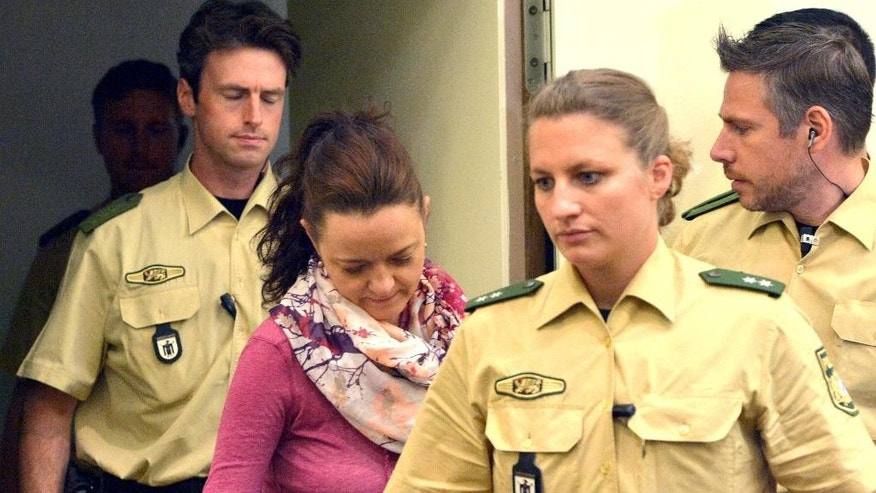 Aug, 6, 2014: Defendant Beate Zschaepe, center, enters the court room at the Higher Regional Court in Munich, Germany. (AP/dpa, Peter Kneffel,file)