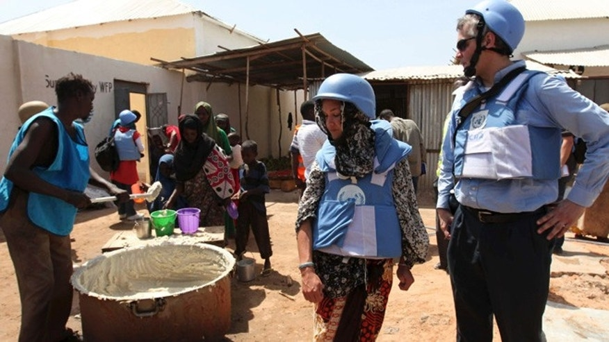Jan 19, 2012: United Nations personnel look on as a worker serves food at a camp in Hodan district in Mogadishu. (Reuters)