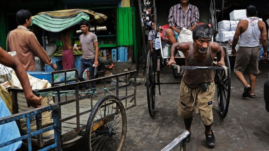 In this Aug. 20, 2014 photo, an Indian hand rickshaw puller with passenger makes his way through a traffic jam in Kolkata, India.  When Prime Minister Narendra Modi swept to power in India's most resounding election victory in decades, he promised to revive the sluggish economy, rein in rising food prices, tackle corruption and overhaul his predecessor's lackluster foreign policy.(AP Photo/ Bikas Das)