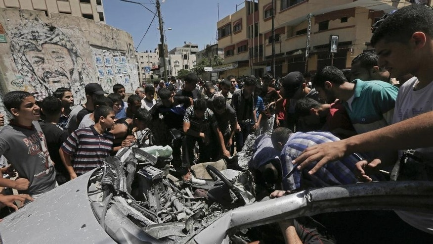 Palestinians inspect the wreckage of a vehicle following an Israeli airstrike at the main street in Gaza City in the northern Gaza Strip, Thursday, Aug. 21, 2014. At least two were killed in the car outside a grocery shop, and a few others were wounded by the Israel airstrike on a Gaza City street, according to the Palestine Red Crescent Society. (AP Photo/Adel Hana)