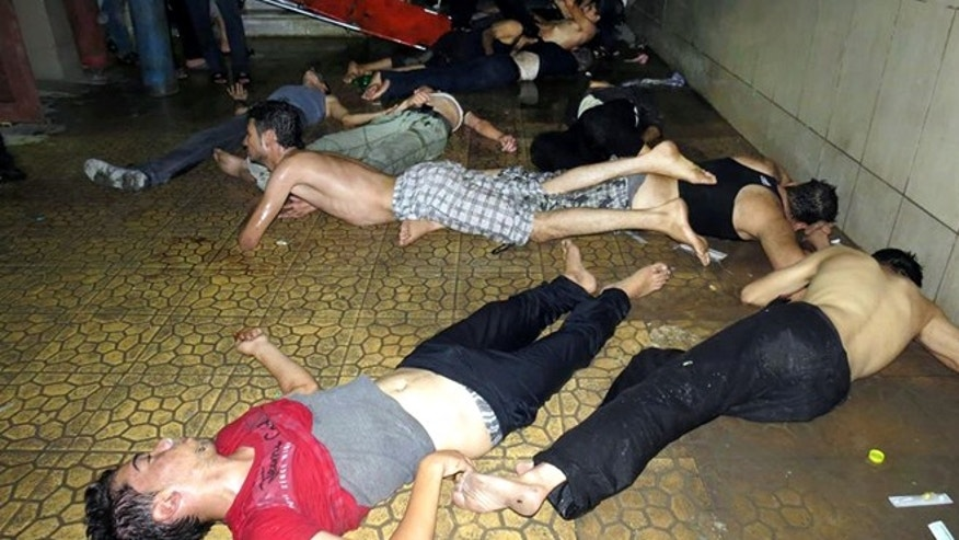 Aug. 21, 2013: This file photo made by a citizen journalist provided by the Media Office Of Douma City which has been authenticated based on its contents and other AP reporting, shows Syrian men lying on the ground as they wait for treatment after an alleged poisonous gas attack fired by regime forces, according to activists in Douma town, Damascus, Syria. An international human rights group says on the anniversary of the deadly chemical attack outside Damascus that justice remains elusive for the victims and their families. (AP/Media Office Of Douma City, File)