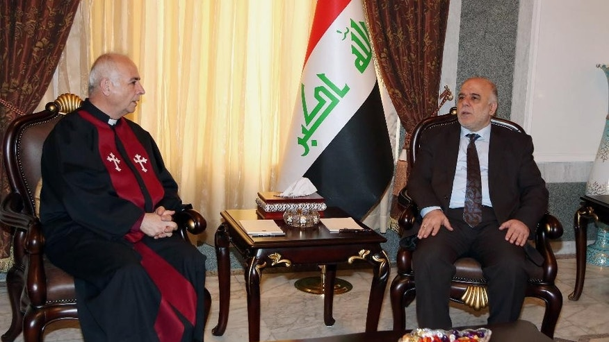 Iraqi premier- designate Haider al-Abadi, right, meets with Pastor Farouk Youssuf in Baghdad, Iraq, Thursday, Aug. 21, 2014. Al-Abadi has until Sept. 11 to submit a list of Cabinet members to parliament for approval. Religious and ethnic minorities have called upon him to assemble an all-inclusive government. (AP Photo/Karim Kadim, Pool)