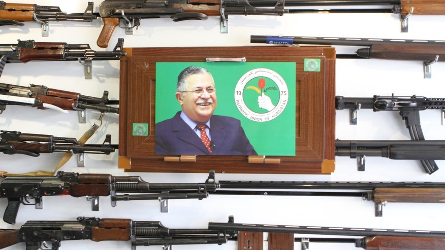 Gun shop in northern Iraqi city of Sulemaniyah displays wares behind photo of Jalal Talabani, founder of the Patriotic Union of Kurdistan. (FoxNews.com)