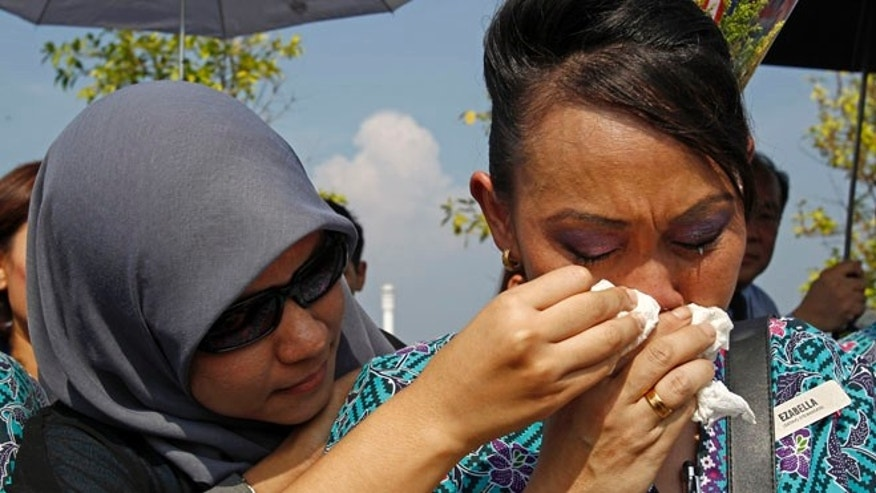 Aug 22, 2014: A Malaysia Airlines crew member cries as she waits outside Bunga Raya Complex at Kuala Lumpur International Airport where victims' bodies of the ill-fated Malaysia Airlines Flight MH17 are to be flown back, in Sepang, Malaysia. (AP)