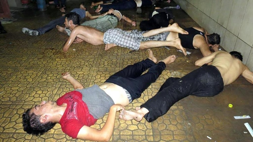 "FILE - This Wednesday, Aug. 21, 2013 file photo made by a citizen journalist provided by the Media Office Of Douma City which has been authenticated based on its contents and other AP reporting, shows Syrian men lying on the ground as they wait for treatment after an alleged poisonous gas attack fired by regime forces, according to activists in Douma town, Damascus, Syria. An international human rights group says on the anniversary of the deadly chemical attack outside Damascus that ""justice remains elusive"" for the victims and their families. (AP Photo/Media Office Of Douma City, File)"
