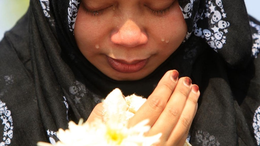 A Muslim woman cries as she waits outside Bunga Raya Complex at Kuala Lumpur International Airport before victims' bodies of the ill-fated Malaysia Airlines Flight MH17 are flown back, in Sepang, Malaysia, Friday, Aug. 22, 2014. The bodies and ashes of 20 Malaysians killed when Malaysian Airlines Flight 17 was shot down over Ukraine in July have arrived in Kuala Lumpur. (AP Photo/Lai Seng Sin)