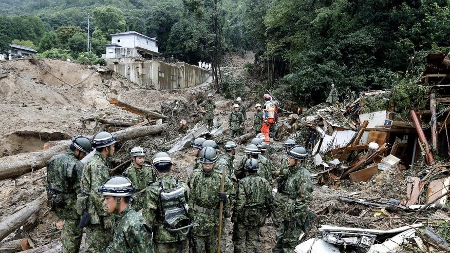 Japan's Self-Defense Force members search for survivors in the rubble in a mud-ridden residential area following a massive landslide in Hiroshima, western Japan, Friday, Aug. 22, 2014.  Hillsides caved in or were swept down into residential areas in at least five valleys in the suburbs of the western Japanese city on Wednesday, crushing dozens of houses after heavy rains.(AP Photo/Kyodo News) JAPAN OUT