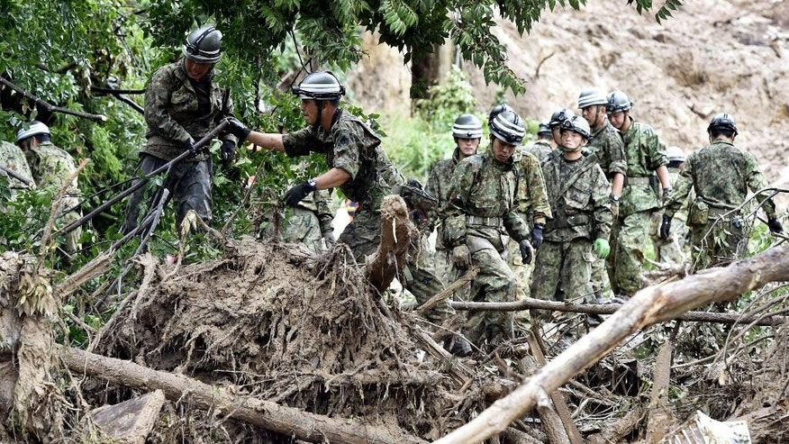 Japan's Self-Defense Force members search for survivors in the rubble in a mud-ridden residential area following a massive landslide in Hiroshima, western Japan, Friday, Aug. 22, 2014.  Japanese police said rain-triggered landslides on the outskirts of Hiroshima city have killed dozens of people. (AP Photo/Kyodo News) JAPAN OUT