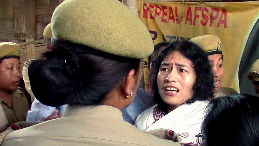 In this Friday, Aug. 22, 2014 photo, Irom Sharmila is detained by policewomen in Imphal, in the northeastern Indian state of Manipur. The frail Indian activist who has been on a hunger strike for nearly 14 years to protest alleged military brutality scuffled with police Friday as they took her back to the same government hospital where she had been force-fed. Sharmila, 42, vowed to continue the hunger strike that landed her in prison for the past 14 years. She walked free on Wednesday after a court threw out the charges of attempted suicide against her. Attempted suicide is a crime in India. (AP Photo/Press Trust of India) INDIA OUT
