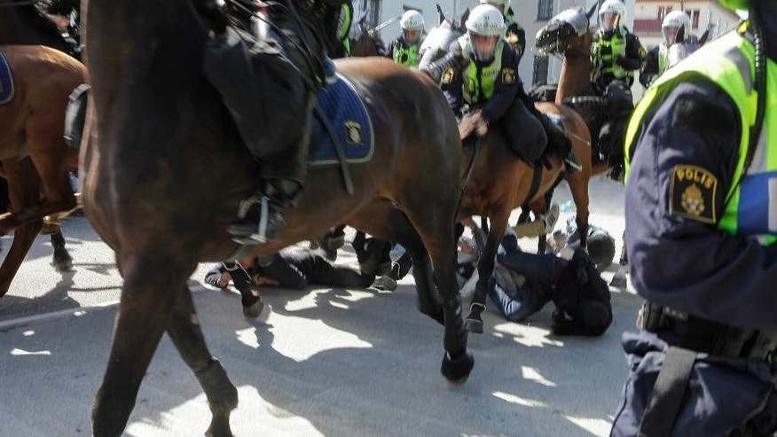 "Police mounted on horses ride through counter-demonstrators protesting against an election meeting arranged by the neo-nazi party ""Svenskarnas Parti"", at a square in central Malmo, Sweden, Saturday, Aug. 23, 2014. Two people were reportedly injured. There were several thousand protesters, while the party meeting totaled less than a hundred sympathizers. (AP Photo/TT News Agency, Drago Prvulovic)   SWEDEN OUT"