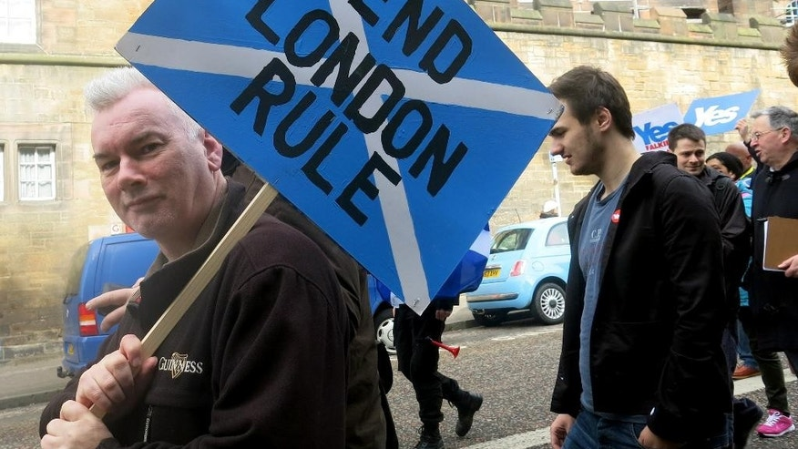 FILE - In this March 15, 2014 file photo, a demonstrator carries a sign during a pro-independence march in Edinburgh, Scotland. A Sept. 18, 2014 referendum will determine if Scotland becomes independent of the United Kingdom. (AP Photo/Jill Lawless)