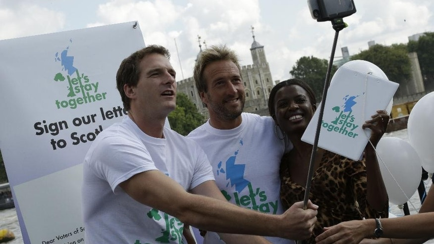 "FILE - In this Thursday, Aug. 7, 2014 file photo, British TV presenters, from left, Dan Snow, Ben Fogle, and June Sarpong take a selfie photo at the launch of their ""Let's Stay Together"" campaign in London, asking Scottish voters to vote against independence in the Scottish independence referendum. A Sept. 18, 2014 referendum will determine if Scotland becomes independent of the United Kingdom. (AP Photo/Matthew Knight)"