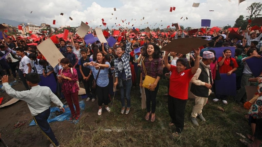 Nepalese celebrate after participating in an attempt to break the record for the largest human national flag, in Katmandu, Nepal, Saturday, Aug. 23, 2014. One of the organizers, Ashish Chaulagai, said more than 38,000 people were estimated to have formed Nepal's flag, shaped as two red triangles with a blue border. Nepal is the only country whose flag is not quadrilateral. The last record was set in Pakistan by 28,957 people. (AP Photo/Bikram Rai)
