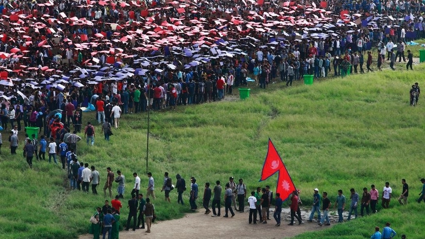 Nepalese arrive to participate in an attempt to break the record for the largest human national flag, in Katmandu, Nepal, Saturday, Aug. 23, 2014. One of the organizers, Ashish Chaulagai, said more than 38,000 people were estimated to have formed Nepal's flag, shaped as two red triangles with a blue border. Nepal is the only country whose flag is not quadrilateral. The last record was set in Pakistan by 28,957 people. (AP Photo/Bikram Rai)