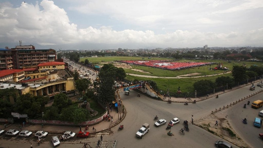 Traffic moves past a field where Nepalese are participating in an attempt to break the record for the largest human national flag, in Katmandu, Nepal, Saturday, Aug. 23, 2014. One of the organizers, Ashish Chaulagai, said more than 38,000 people were estimated to have formed Nepal's flag, shaped as two red triangles with a blue border. Nepal is the only country whose flag is not quadrilateral. The last record was set in Pakistan by 28,957 people. (AP Photo/Bikram Rai)