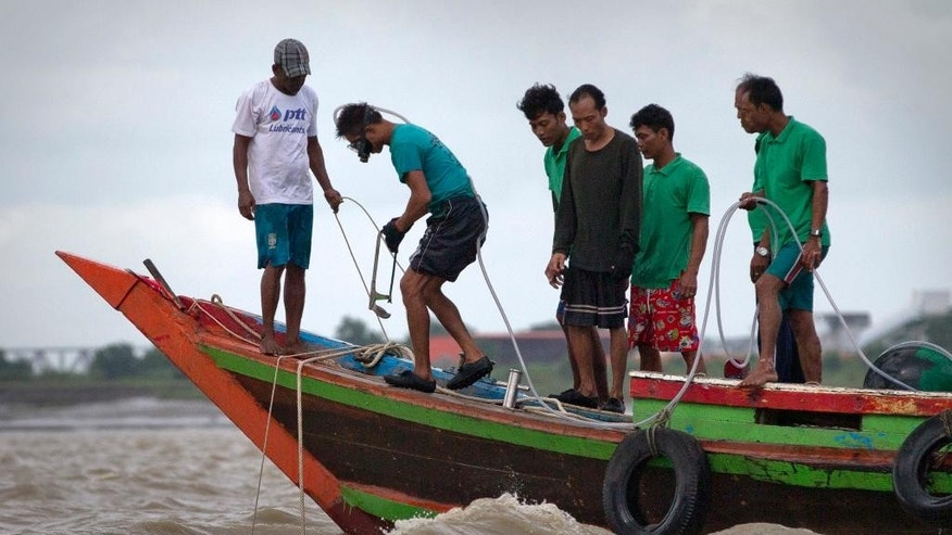 In this Aug 15, 2014 photo, a diver, second from left, clings to a rubber hoses that act as primitive breathing device prepares to dive searching for an ancient bell in Yangon River in Yangon, The world's largest copper bell, believed to have been lying deep beneath the riverbed for more than four centuries. Numerous efforts to locate it, with the help of high-tech equipment have failed, and some historians now question whether it exists at all. (AP Photo/Gemunu Amarasinghe)