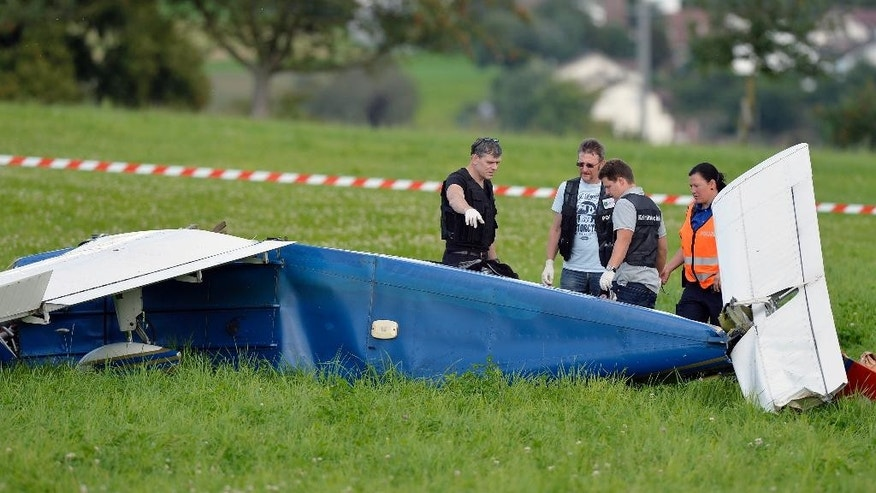 Police inspect the wreckage of a small plane that collided with another plane and crashed  during an  emergency landing  near Moerikon, Switzerland, Sunday Aug. 24, 2014. Police say two small planes have  collided over northeastern Switzerland, injuring seven people.St.  Gallen canton (state) police said the aircraft both made emergency landings  after Sunday's collision- one in a field and the other at an airfield. The pilot and three passengers aboard the plane that landed in the field were seriously injured. The pilot of the other plane and its two passengers also were injured.There  was no word on the cause of the collision.   (AP Photo/Keystone, Walter Bieri)