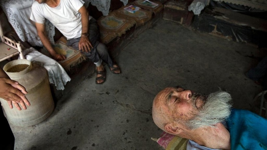 """In this photo taken Thursday, July 17, 2014,  a Uighur man prepares to get his beard massaged at a barber shop in the city of Aksu in western China's Xinjiang province.  In China's restive western province of Xinjiang, young men of the Uighur ethnic minority are not allowed to have beards. Also proscribed are certain types of women's headscarves, veils and """"jilbabs,"""" loose, full-length garments worn in public. Such restrictions are not new but their enforcement has intensified this year in the wake of attacks Beijing has blamed on religious extremists. (AP Photo/Ng Han Guan)"""