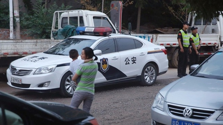 August 23, 2014: Chinese security guards stand on duty near a police car at a junction leading to the venue for the Beijing Independent Film Festival.  Chinese authorities blocked the annual independent film festival from opening on Saturday, said organizers of an event that has become a rare and influential venue for the showing of films that could be critical of the government. (AP Photo/Ng Han Guan)