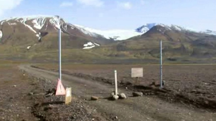 In an image from an Aug. 19, 2014 video, a sign is posted on the road next to Bardarbunga, a subglacial stratovolcano located under Iceland's largest glacier.  (AP/Courtesy Channel 2 Iceland)