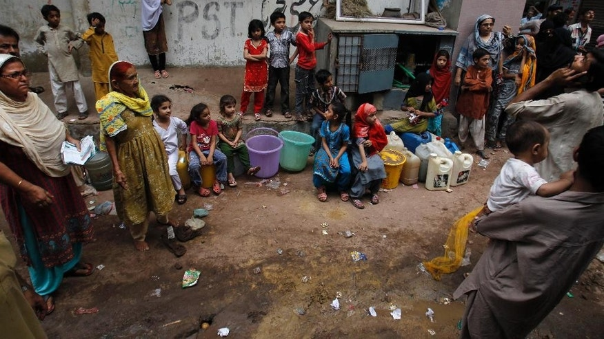 In this Wednesday, May 14, 2014 photo, Pakistani women and children gather near a water distribution point hoping for the water to come back after being cut, in Karachi, Pakistan. On the outskirts of the slums of Pakistan's biggest city, protesters burning tires and throwing stones have what sounds like a simple demand: They want water at least once a week. As the city of roughly 18 million people rapidly grows, the water shortages are only expected to get worse. (AP Photo/Fareed Khan)