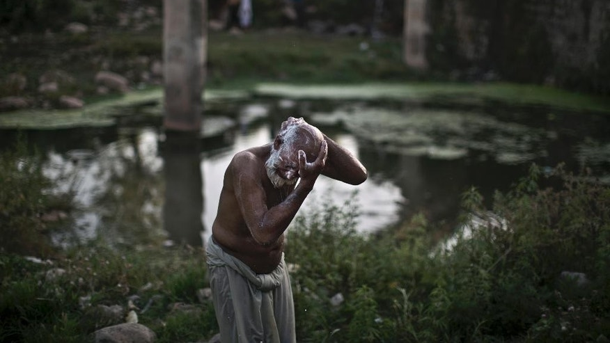 In this Tuesday, May 27, 2014 photo, Pakistani vegetable vendor Sher Khan, 55, applies soap to his body while bathing near a water supply pipe, near Islamabad, Pakistan. On the outskirts of the slums of Pakistan's biggest city, protesters burning tires and throwing stones have what sounds like a simple demand: They want water at least once a week. Karachi gets most of its water from the Indus River - about 550 million gallons per day - and another 100 million gallons from the Hub Dam that is supplied by water from neighboring Baluchistan province. But in recent years, drought has hurt the city's supply. (AP Photo/Muhammed Muheisen)
