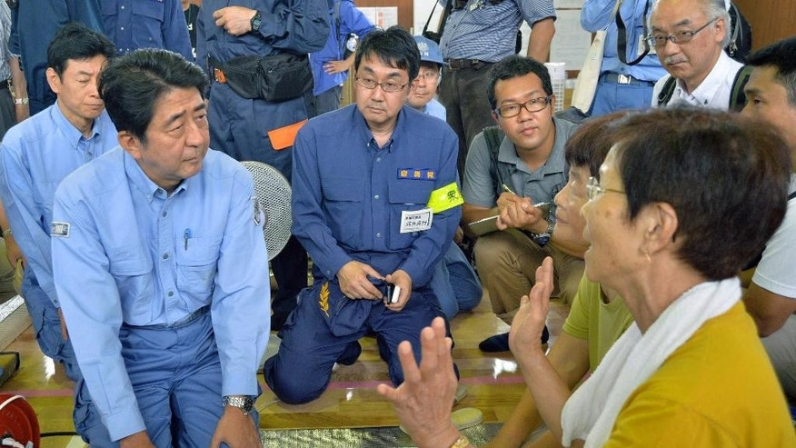 Japan's Prime Minister Shinzo Abe, left, listens to a victim at an evacuation center in Hiroshima, western Japan Monday, Aug. 25, 2014. Abe is visiting Hiroshima to see search and cleanup operations following landslides around the city that killed at least 50 people. (AP Photo/Kyodo News) JAPAN OUT, MANDATORY CREDIT