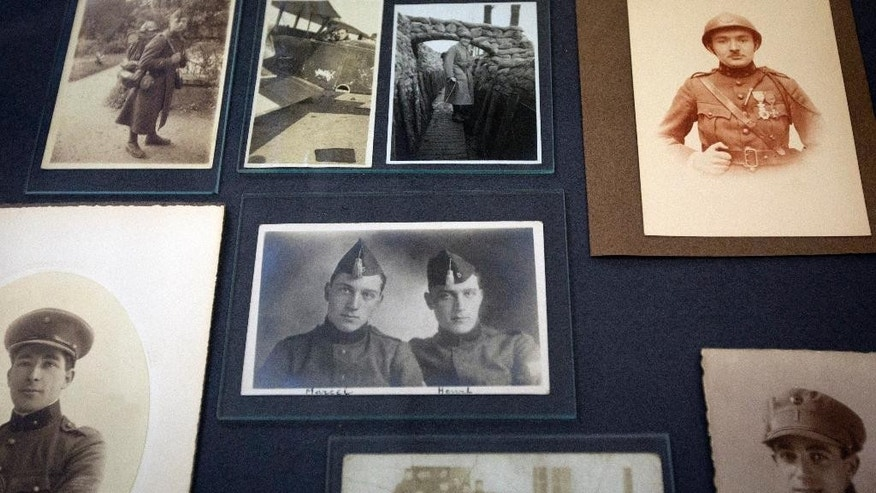 In this photo taken on Thursday, Aug. 21, 2014, pictures of university students who served during World War I are on display at the Leuven University Library in Leuven, Belgium. The German invading forces set the heart of Leuven alight during the early days of World War I, paying special attention to the gem of learning and history, the university library. (AP Photo/Virginia Mayo)