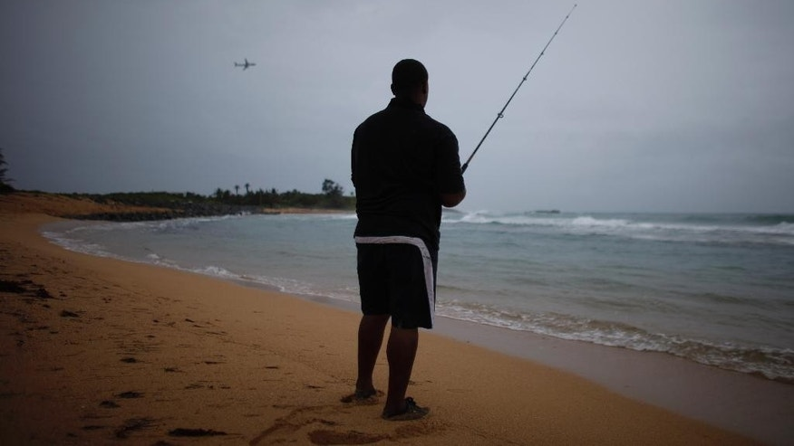 A man fishes as a cluster of storms passes through the area, in San Juan, Puerto Rico, Friday, Aug. 22, 2014. The National Weather Service in San Juan said the region could be hit with up to 6 inches (15 centimeters) of rain and wind gusts of 35 mph (56 kph). (AP Photo/Ricardo Arduengo)