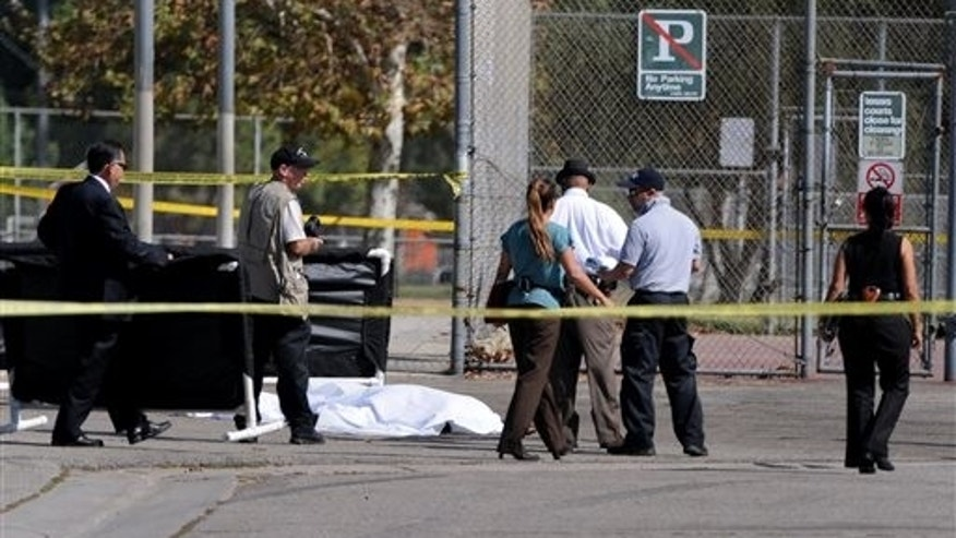 Officers investigate the scene of a shooting Sunday, Aug. 24, 2014, where one person was killed in Sylmar, Calif.