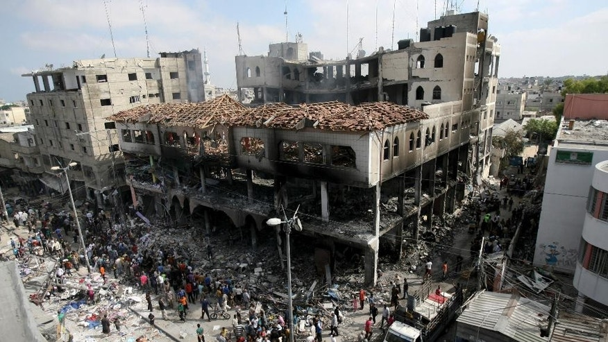 Palestinians inspect the damage of a Rafah commercial center after an Israeli strike in Rafah, in the southern Gaza Strip, Sunday, Aug. 24, 2014. The Gaza police operation room reported three airstrikes on a Rafah commercial center, which consists of two floors and includes 100 shops. The building almost collapsed and a huge fire erupted in the shops. (AP Photo/Eyad Baba)