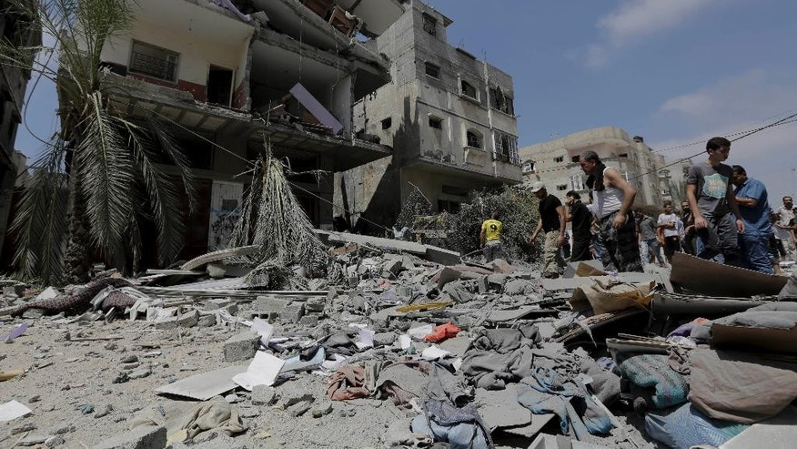 Palestinian relatives salvage belongings from the rubble of a three-story building belonging to the Abdul Hadi family damaged after an Israeli strike in Gaza City in the northern Gaza Strip, Sunday, Aug. 24, 2014. (AP Photo/Adel Hana)