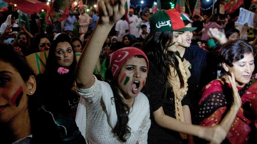 Supporters of Pakistan's cricketer turned-politician Imran Khan rally in Karachi, Pakistan, Friday, Aug. 22, 2014.  Thousands of Khan's and cleric Tahir-ul-Qadri's supporters are besieging parliament in the capital to pressure Prime Minister Nawaz Sharif to resign over alleged election fraud. (AP Photo/Shakil Adil)