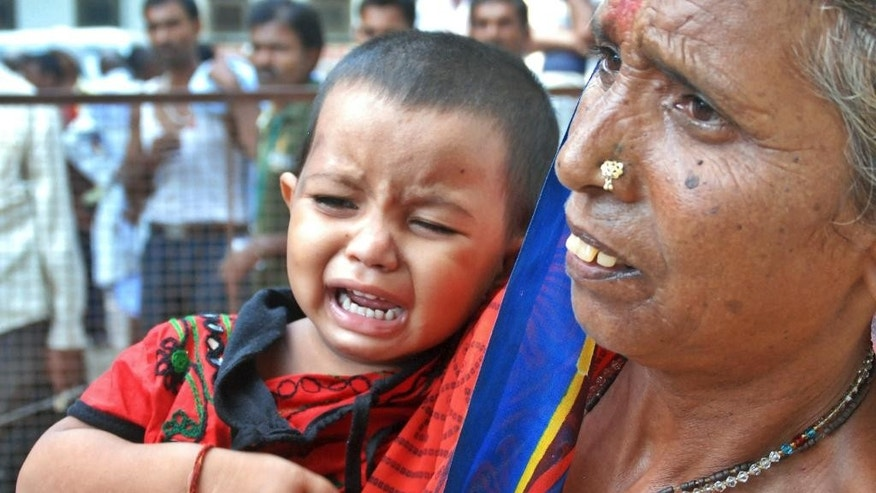 A woman holds a crying child as relatives of victims gather at the spot of a stampede at the Kamta Nath Hindu temple in Chitrakoot, India, Monday, Aug. 25, 2014. A pre-dawn stampede killed 10 people Monday as tens of thousands of Hindus were worshipping in an annual procession marking the holy day of Somvati Amavasya. (AP Photo/Amar Deep)