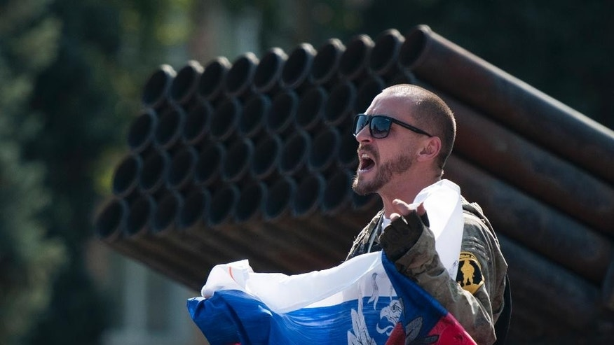 A pro-Russian rebel holds a Russian national flag near to damaged heavy hardware from the Ukrainian army during an exhibition in the central square in Donetsk, eastern Ukraine, Sunday, Aug. 24, 2014. Ukraine has retaken control of much of its eastern territory bordering Russia in the last few weeks, but fierce fighting for the rebel-held cities of Donetsk and Luhansk persists. (AP Photo/Antoine E.R. Delaunay)