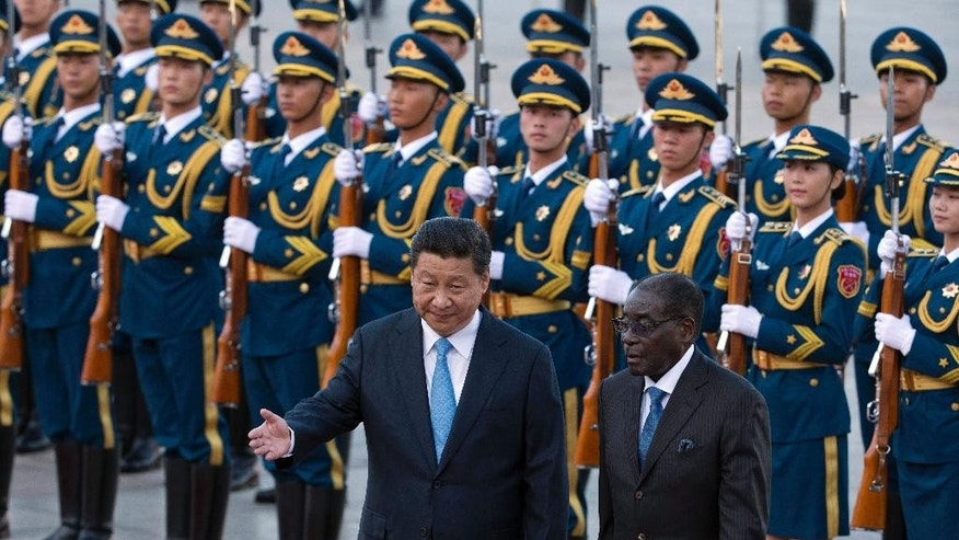 Chinese President Xi Jinping, left shows Zimbabwe's President Robert Mugabe the way during a welcome ceremony outside the Great Hall of the People in Beijing, China, Monday, Aug. 25, 2014. (AP Photo/Ng Han Guan)