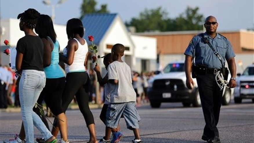 Protesters walk across the street carrying roses past a member of the Missouri Highway Patrol Monday, Aug. 18, 2014, in Ferguson, Mo.