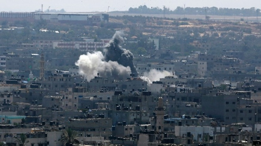 Aug. 26, 2014: Smoke and dust rise after an Israeli strike hits in Gaza City, northern Gaza Strip. The latest strikes came as Egypt urged Israel and Hamas to resume indirect talks on a permanent cease-fire, based on an Egyptian proposal for a new border deal for blockaded Gaza.