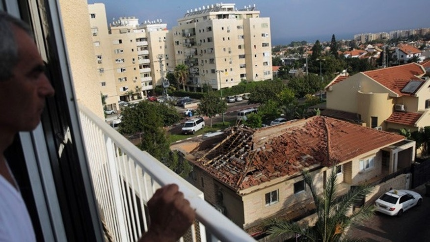 August 26, 2014: A man looks at a home hit by a rocket fired from the northern Gaza Strip Tuesday morning in the costal city of Ashkelon, Israel. (AP Photo/Tsafrir Abayov)