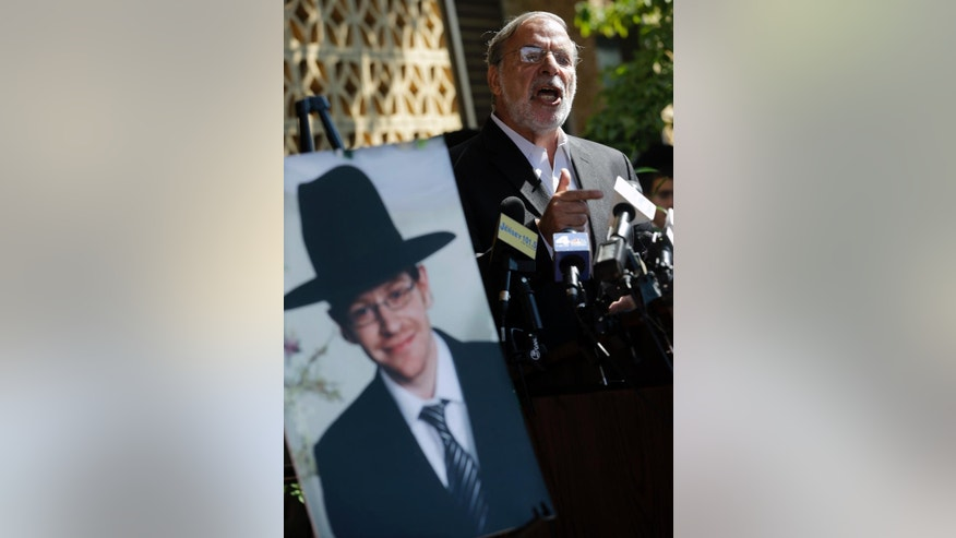 New York assemblyman Dov Hikind addresses a gathering as he stands near a photograph of Aaron Sofer, 23, Tuesday, Aug. 26, 2014, in Lakewood, N.J. Israeli police said Tuesday they are searching for the young New Jersey religious student who went missing in Israel during a hike in a forest outside Jerusalem last week. Sofer of Lakewood, New Jersey, has been missing since Friday when he went on a hike with a friend in the Jerusalem Forest, said police spokesman Micky Rosenfeld. (AP Photo/Mel Evans)