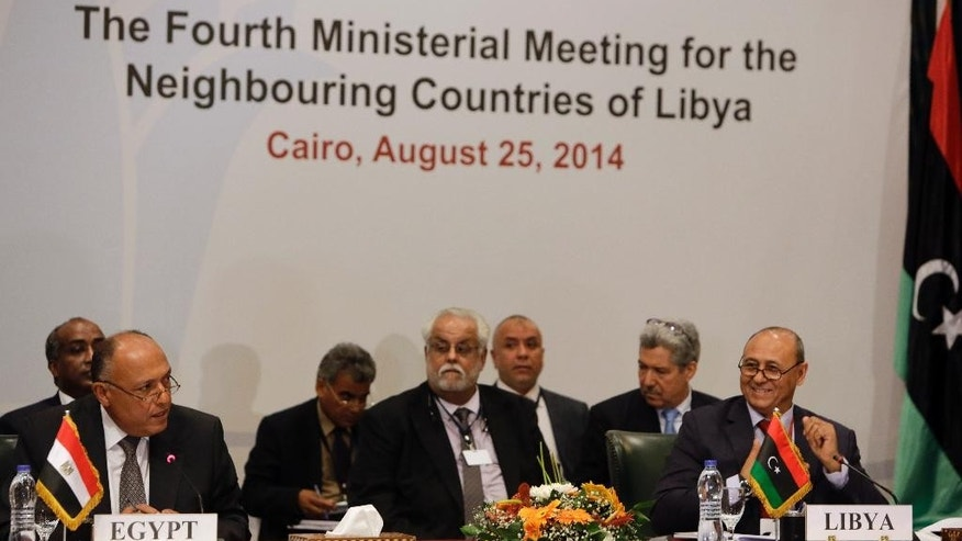 Libyan Foreign Minister Mohamed Abdelaziz, right, listens to his Egyptian counterpart Sameh Shukri, left, during the opening session of The Fourth Ministerial Meeting for the Neighbouring Countries of Libya, in Cairo, Egypt, Monday, Aug. 25, 2014. Foreign ministers from Egypt, Libya, Algeria, Tunisia, Sudan, Chad, as well as the Arab League Secretary General met Monday in Cairo as Islamist-led militias in the Libyan capital say they consolidated their hold on Tripoli and its international airport, driving out rivals to the city's outskirts after battles that largely destroyed the strategic hub. (AP Photo/Amr Nabil)