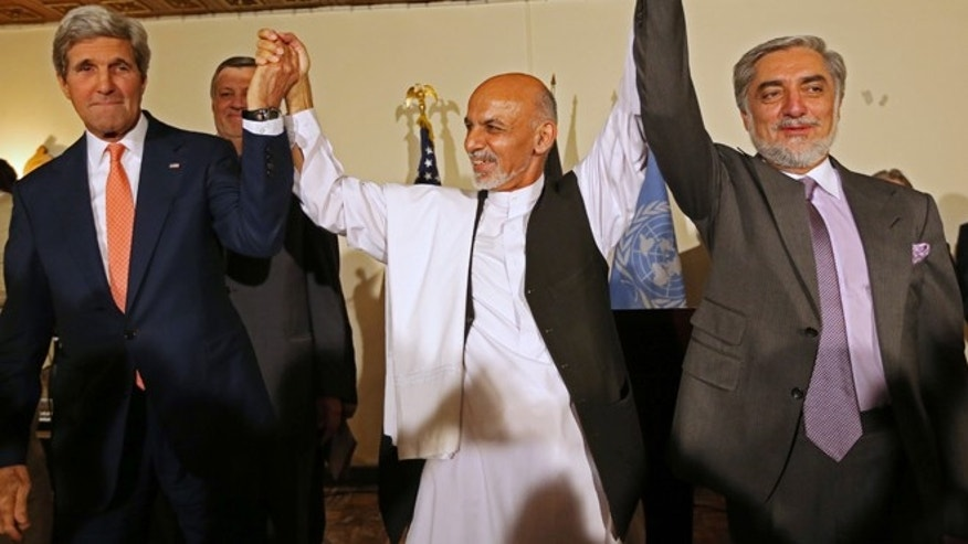 This July 12, 2014 file photo shows. from left, Secretary of State John Kerry, Afghanistan's presidential candidate Ashraf Ghani Ahmadzai, and Afghan presidential candidate Abdullah Abdullah during a joint news conference in Kabul, Afghanistan.