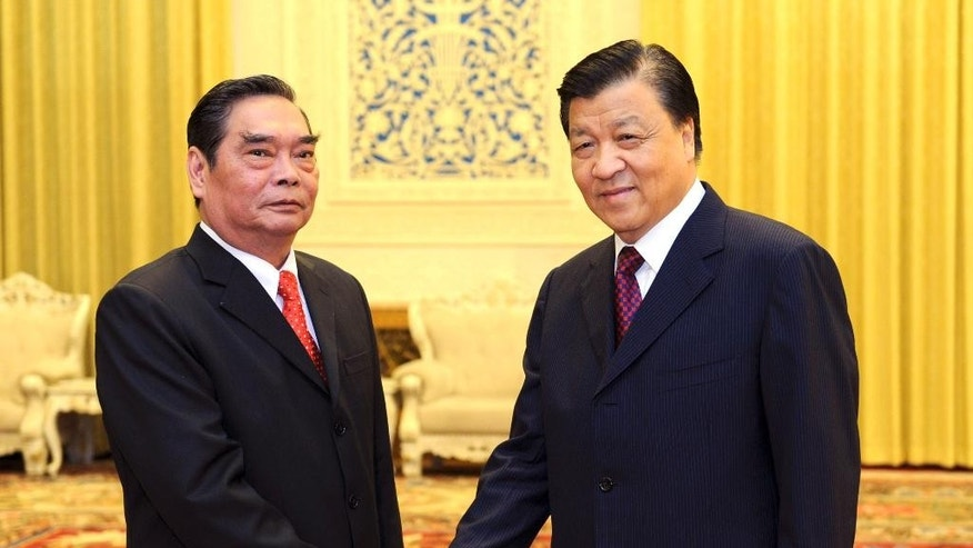 In this photo released by China's Xinhua news agency, Vietnamese special envoy Le Hong Anh, left, poses with Liu Yunshan, a member of the Standing Committee of the Political Bureau of the Communist Party of China (CPC) Central Committee, prior to a meeting in Beijing Wednesday, Aug. 27, 2014. China and Vietnam said they're committed to negotiating maritime disputes to avoid a recurrence of tensions that spiked when China deployed an oil rig in waters claimed by Hanoi. (AP Photo/Xinhua, Zhang Duo) NO SALES