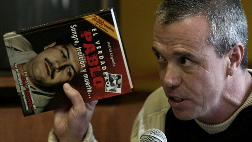 FILE - In this  June 27, 2006, file photo, John Jairo Velasquez, a former hit man for Pablo Escobar, gives his testimony while holding a book titled 'The True Pablo, Blood, Treason, and Death' during the trial against Alberto Santofimio Botero in Bogota, Colombia. (AP Photo/ William Fernando Martinez, File)