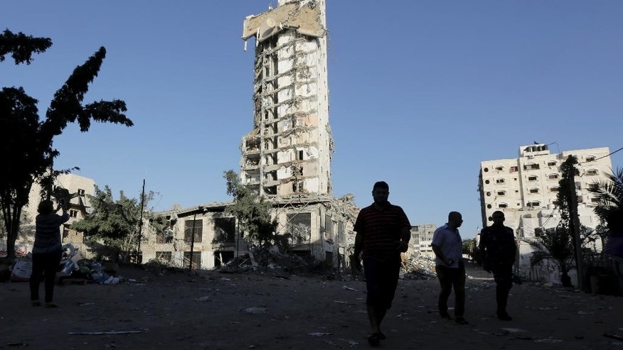 Palestinians walk in front of the damage to the Italian Complex following several late night Israeli airstrikes in Gaza City, in the northern Gaza Strip, Tuesday, Aug. 26, 2014. Israel bombed two Gaza City high-rises with dozens of homes and shops Tuesday, collapsing the 15-storey Basha Tower and severely damaging the Italian Complex in a further escalation in seven weeks of cross-border fighting with Hamas. (AP Photo/Adel Hana)