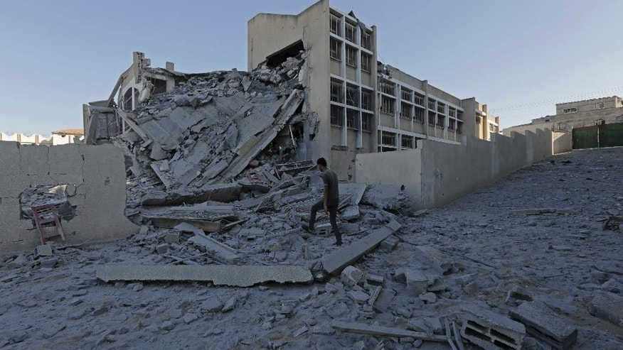 Palestinian youth inspect the damage of Ali Ibn Abi Talib government school after it was hit overnight in an Israeli strike in Gaza City, in the northern Gaza Strip, Tuesday, Aug. 26, 2014. (AP Photo/Adel Hana)